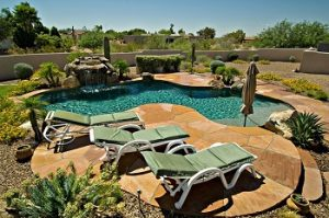 An image of a backyard in the Phoenix area that includes a pool and desert landscaping, which can also benefit from fertilization.